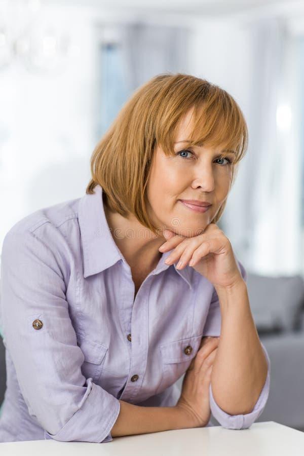 Retrato da mulher madura com mão no queixo que senta-se na tabela na casa foto de stock