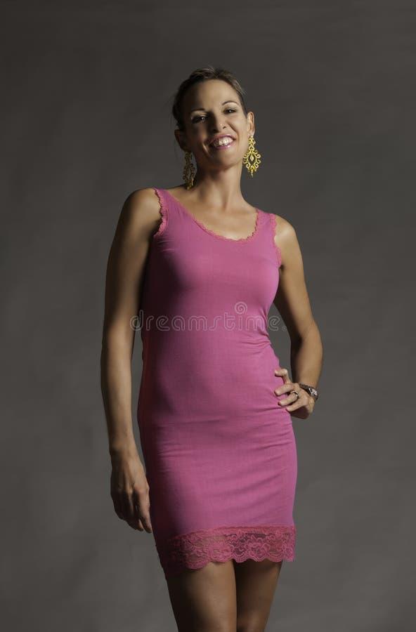 Retrato da mulher madura de riso bonita no minidress cor-de-rosa foto de stock royalty free