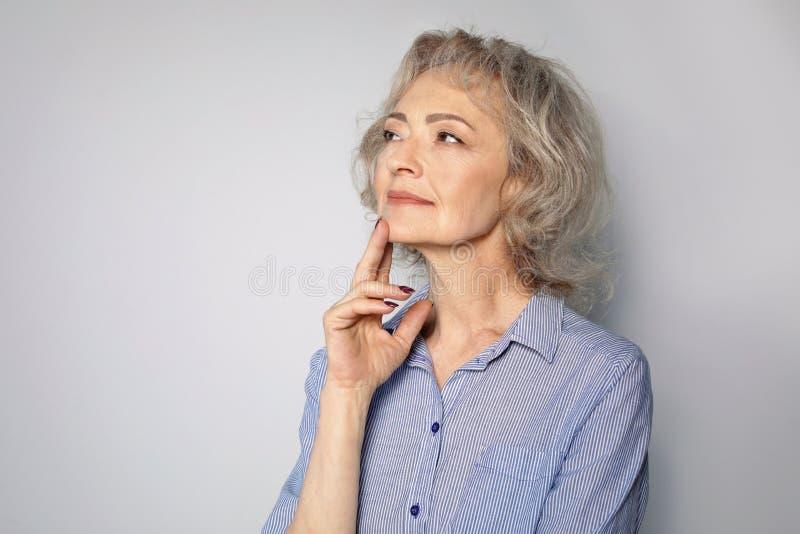 Retrato da mulher madura no fundo cinzento fotografia de stock royalty free