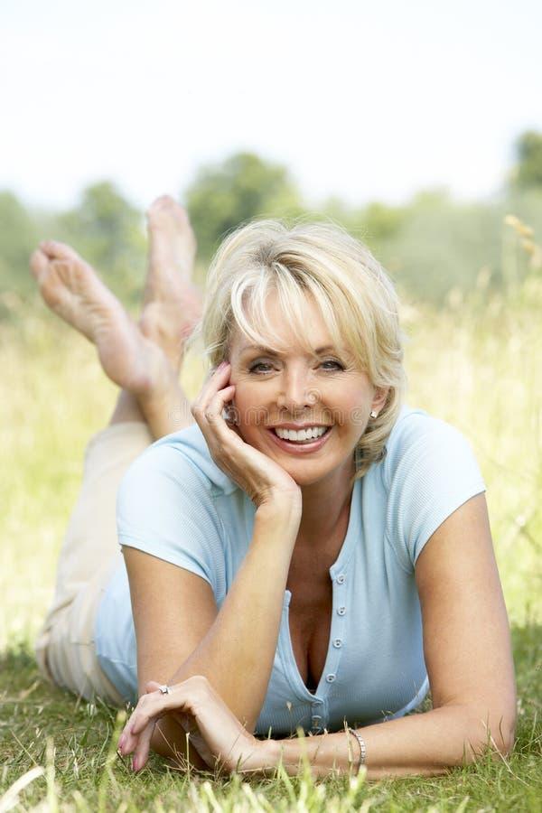 Retrato da mulher madura que relaxa no campo foto de stock royalty free