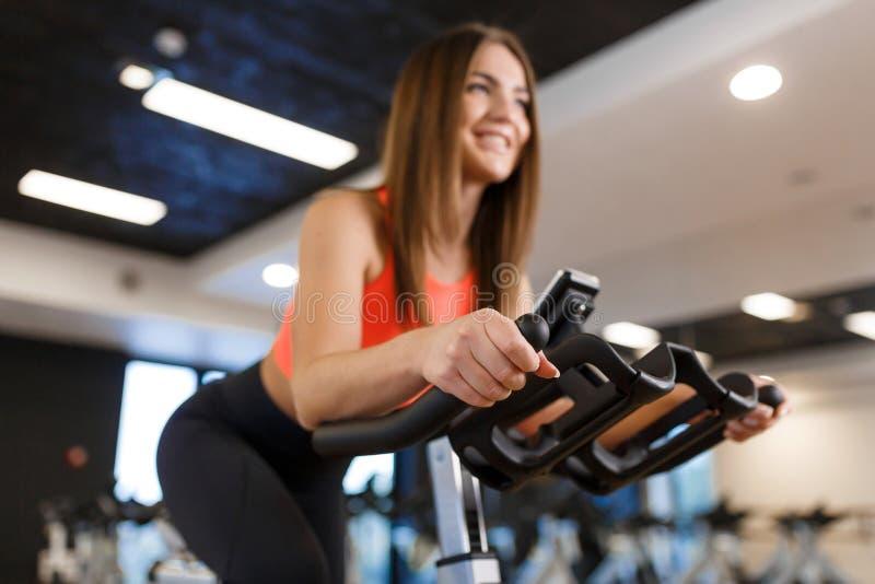 Retrato da mulher magro nova no exerc?cio do sportwear na bicicleta de exerc?cio no gym Conceito do estilo de vida do esporte e d fotos de stock royalty free