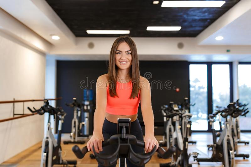 Retrato da mulher magro nova no exerc?cio do sportwear na bicicleta de exerc?cio no gym Conceito do estilo de vida do esporte e d fotos de stock