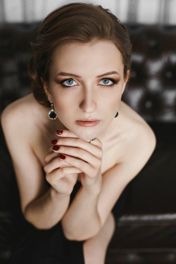 Retrato da mulher modelo moreno nova elegante e bonita com composição delicada, olhos azuis e penteado elegante, no bla longo imagem de stock