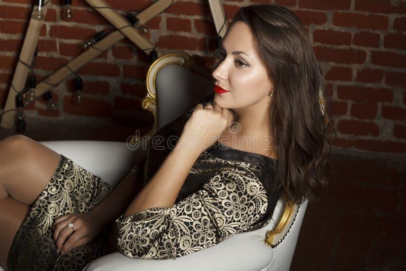 Retrato da mulher moreno bonita nova que senta-se na cadeira como a fotografia de stock