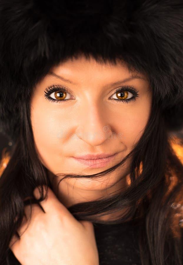 Retrato da mulher moreno bonita nova que veste o chapéu peludo Forma macia da beleza do inverno da pele imagem de stock