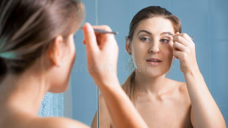 Retrato da mulher moreno bonita que arranca as sobrancelhas com pinça fotos de stock