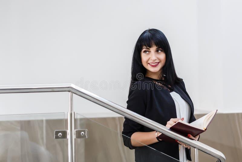 Retrato da mulher moreno feliz bonita nova vestida em um terno de negócio preto que trabalha com um caderno, estando no escritóri imagens de stock