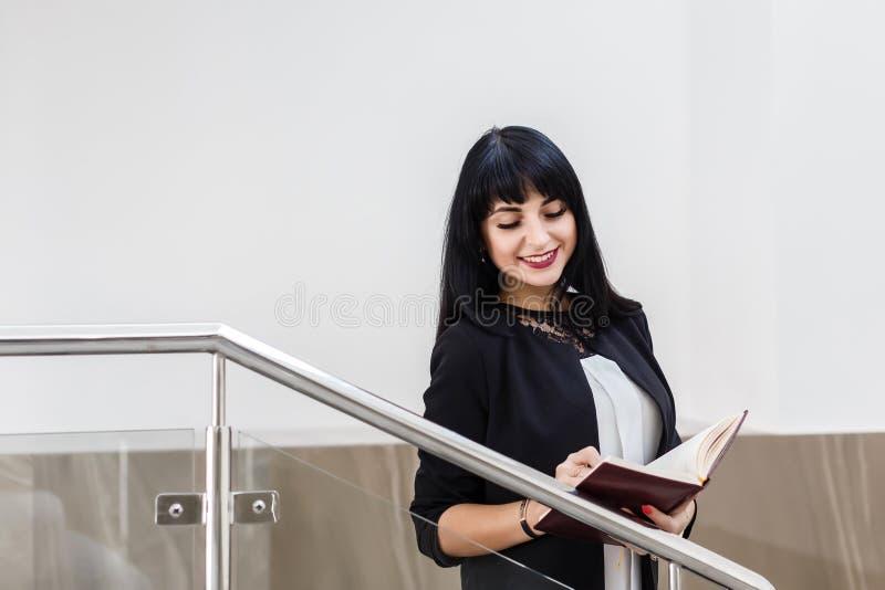 Retrato da mulher moreno feliz bonita nova vestida em um terno de negócio preto que trabalha com um caderno, estando no escritóri foto de stock royalty free