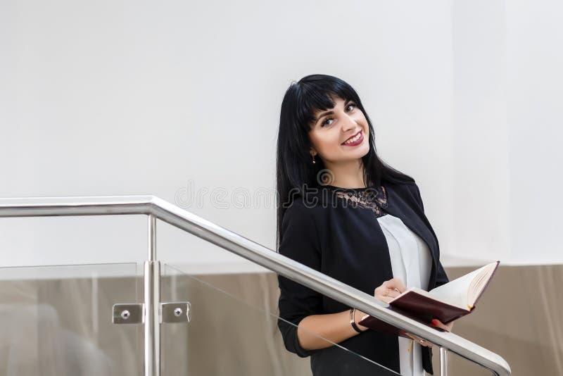 Retrato da mulher moreno feliz bonita nova vestida em um terno de negócio preto que trabalha com um caderno, estando no escritóri fotografia de stock royalty free