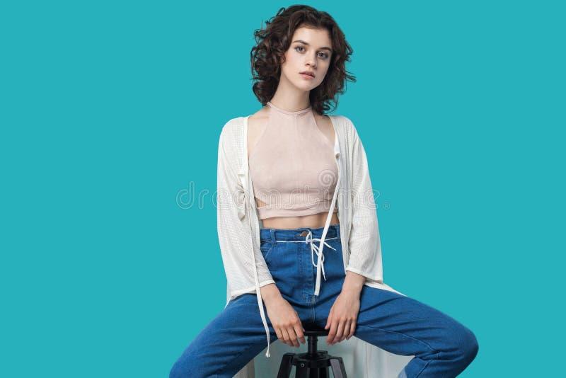 Retrato da mulher moreno nova bonita calma séria no estilo ocasional que senta-se na cadeira e que olha a câmera com cara séria fotos de stock