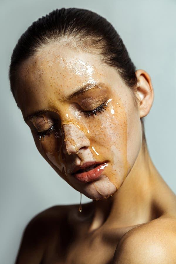Retrato da mulher moreno nova bonita com sardas e mel na cara com olhos fechados e a cara s?ria imagem de stock