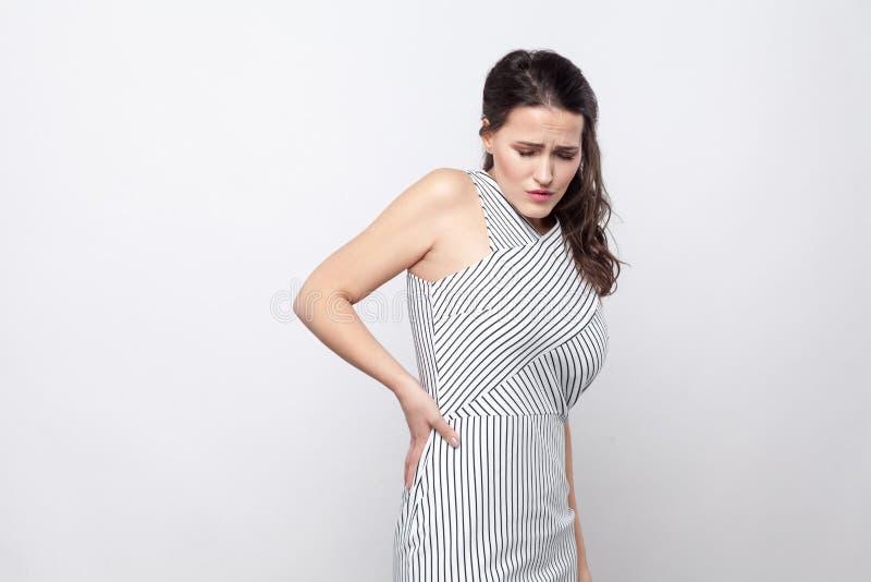 Retrato da mulher moreno nova bonita infeliz triste com composição e posição listrada do vestido com dor da espinha ou do rim e imagens de stock