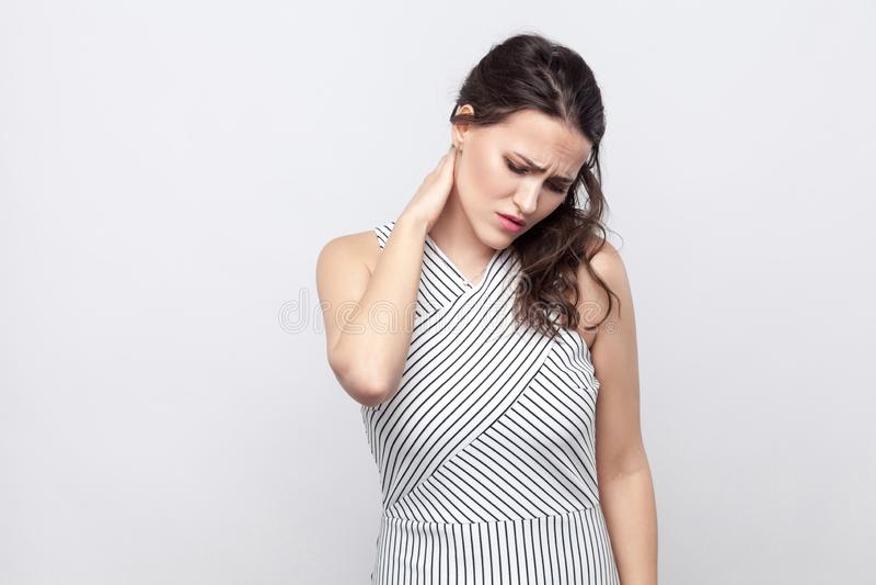 Retrato da mulher moreno nova doente com a composição e a posição listrada do vestido que guardam seu pescoço e que sentem a dor fotos de stock royalty free