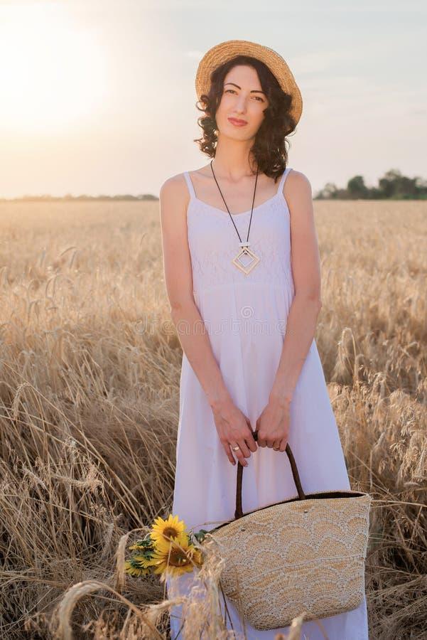 Retrato da mulher moreno nova no chapéu de palha no campo de trigo com saco e girassóis da palha fotografia de stock