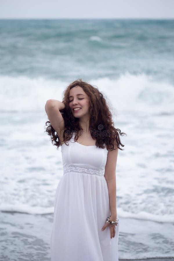 Retrato da mulher moreno nova que aprecia a tempestade do mar fotos de stock royalty free