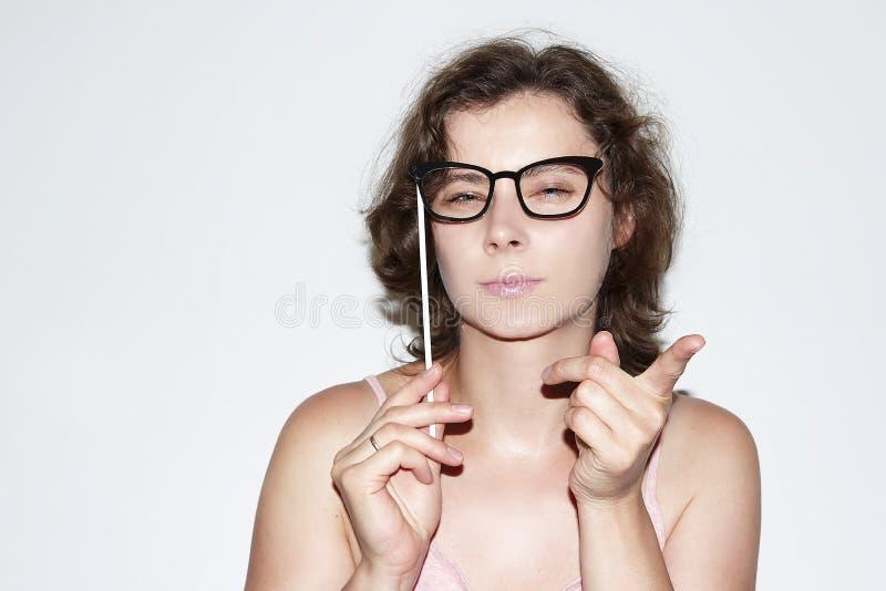 Retrato da mulher moreno 'sexy' atrativa com máscara dos vidros na vara A menina bonita aponta o dedo foto de stock