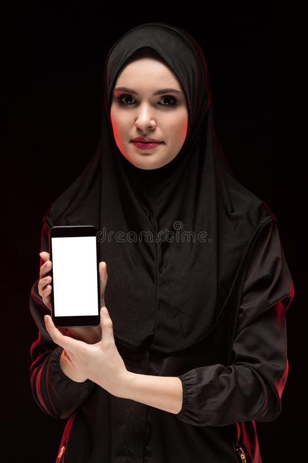 Retrato da mulher muçulmana nova esperta bonita que veste o telefone celular preto da propaganda do hijab em suas mãos como a edu imagens de stock