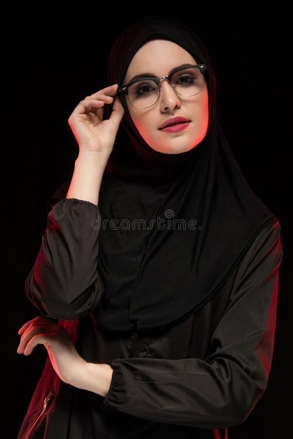 Retrato da mulher muçulmana nova na moda bonita que veste o hijab e vidros pretos como o levantamento oriental moderno do conceit foto de stock royalty free