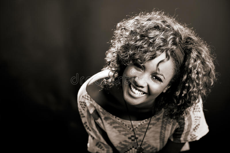 Mulher negra bonita no fundo preto. Tiro do estúdio imagens de stock