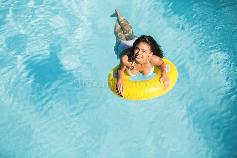 Retrato da mulher no biquini branco que flutua no tubo inflável na piscina fotografia de stock royalty free