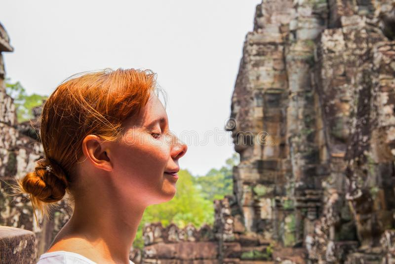 Retrato da mulher no templo de Bayon, Siem Reap, Camboja Cara da jovem mulher e cara da estátua imagem de stock royalty free