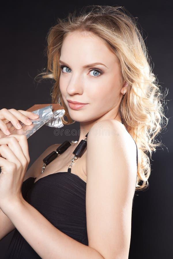 Retrato da mulher nova bonita com um chocolate foto de stock