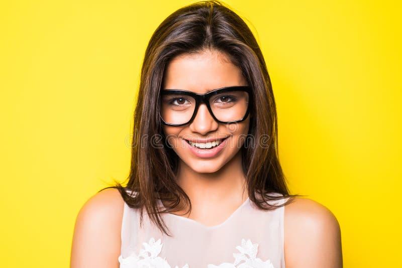 Retrato da mulher nova bonita de sorriso Menina com monóculos vestindo Fundo amarelo imagem de stock royalty free