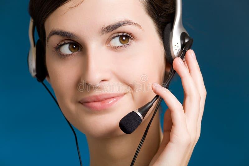 Retrato da mulher nova com auriculares, no fundo azul, sorrindo imagem de stock