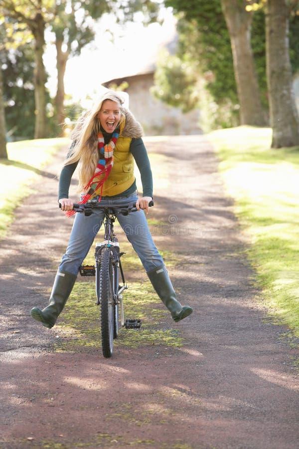 Retrato da mulher nova com ciclo no parque do outono foto de stock