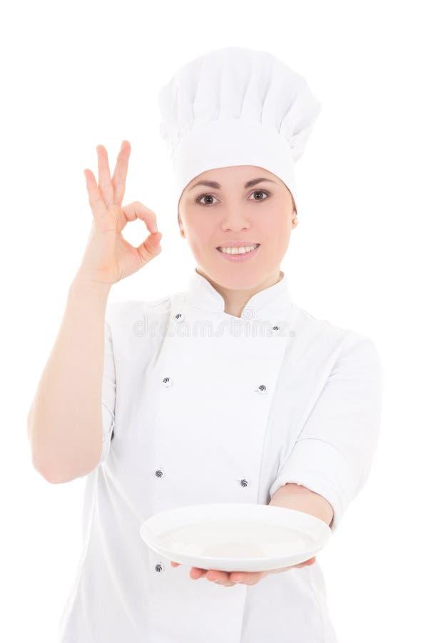 Retrato da mulher nova do padeiro no uniforme com showin vazio da placa fotos de stock