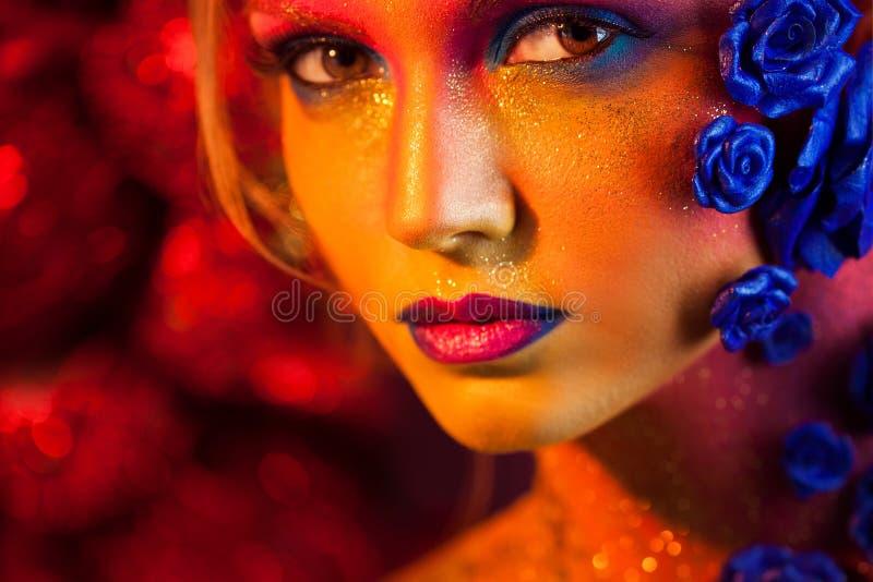 Retrato da mulher nova e atrativa com composição da arte Cores impetuosas, brilho na cara e decoração floral imagens de stock royalty free