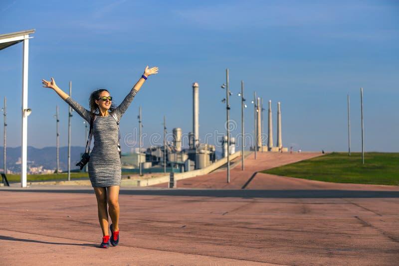 Retrato da mulher nova e atrativa que está no parque urbano com mãos acima levantadas fotografia de stock royalty free
