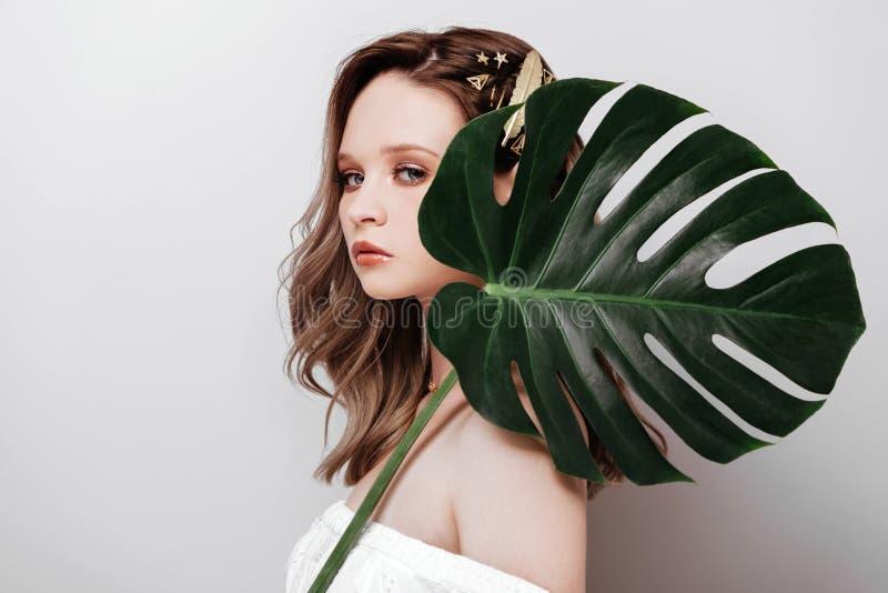 Retrato da mulher nova e bonita nas folhas tropicais imagem de stock royalty free