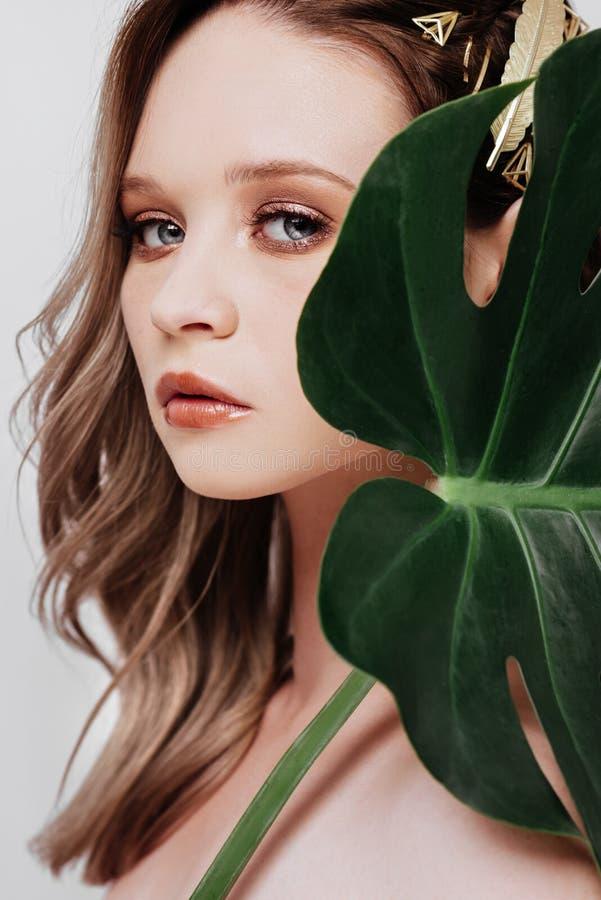 Retrato da mulher nova e bonita nas folhas tropicais foto de stock royalty free