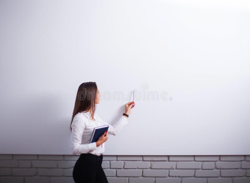 Retrato da mulher nova feliz da mulher de negócios perto na parede branca fotos de stock