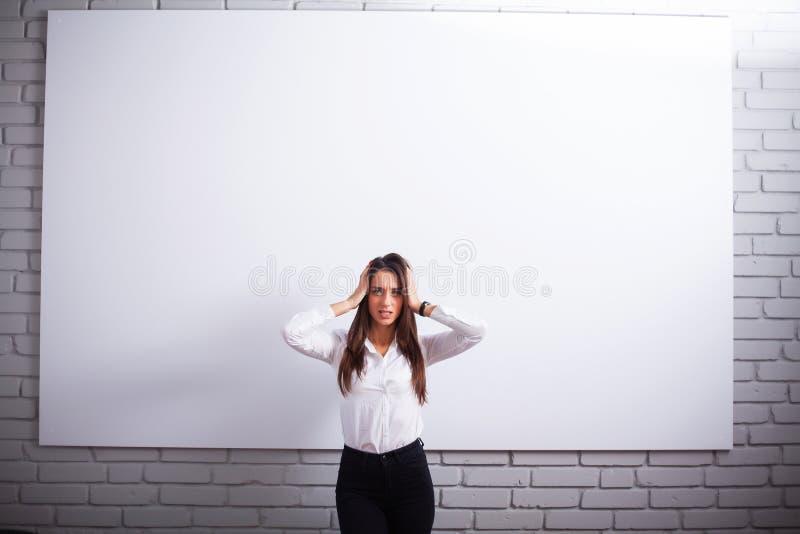 Retrato da mulher nova feliz da mulher de negócios perto na parede branca foto de stock royalty free