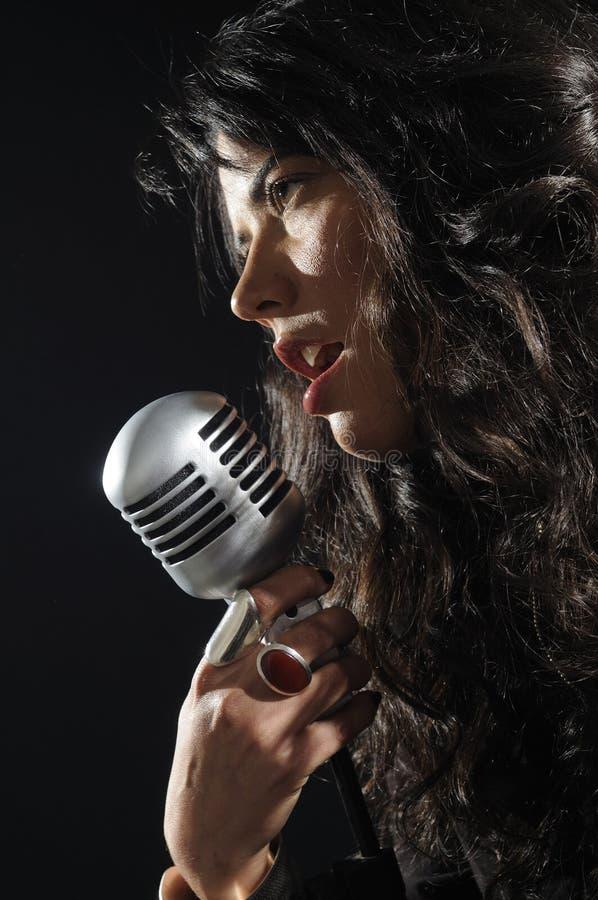 Retrato da mulher nova que canta com mic retro fotos de stock royalty free