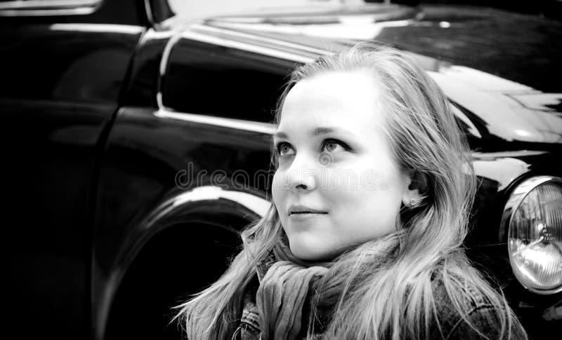 Retrato da mulher nova que senta-se de encontro ao carro retro imagem de stock