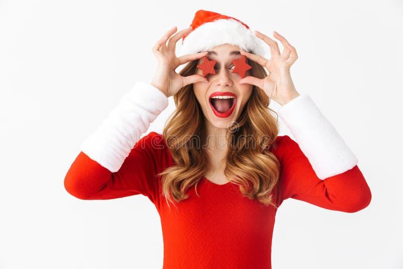 Retrato da mulher otimista 20s que veste o traje vermelho de Santa Claus que sorri e que guarda decorações do Natal, isolado sobr imagens de stock royalty free