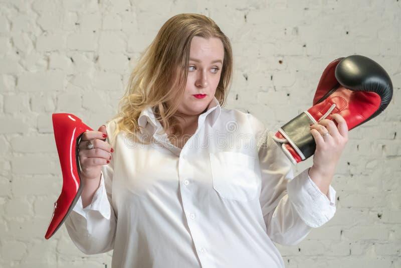 Retrato da mulher positiva atrativa do tamanho que tem as emoções da escolha isoladas sobre o fundo branco Uma menina em uma cami imagens de stock