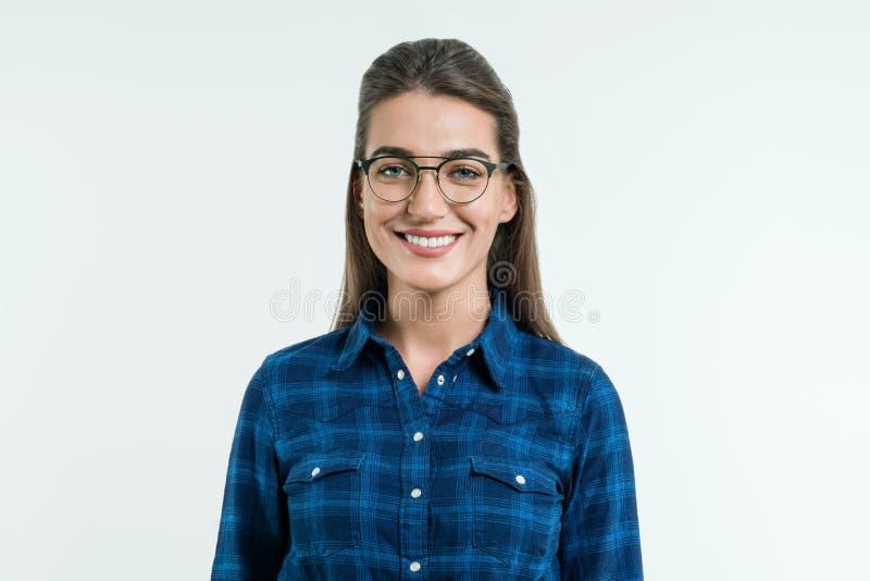 Retrato da mulher positiva nova com cabelo reto longo, olhos azuis e um sorriso atrativo, levantando no estúdio no backgro branco imagens de stock royalty free