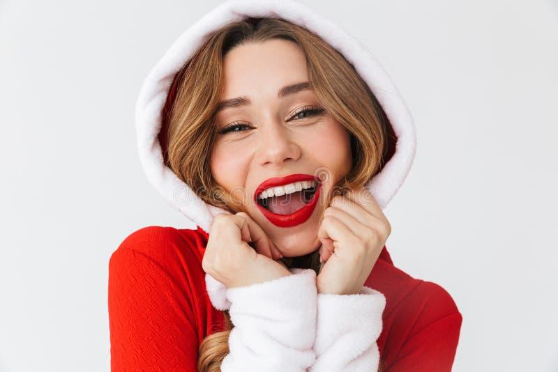 Retrato da mulher positiva 20s que veste o traje vermelho de Santa Claus que sorri e que está, isolado sobre o fundo branco foto de stock royalty free