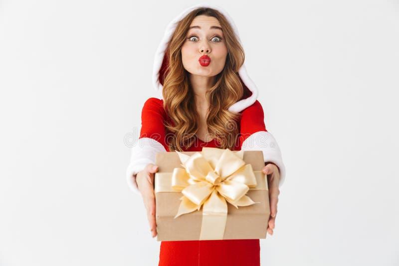 Retrato da mulher positiva 20s que veste o traje vermelho de Santa Claus que sorri e que guarda a caixa atual, isolado sobre o fu imagens de stock