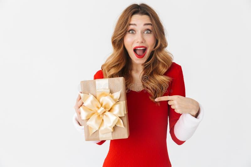 Retrato da mulher positiva 20s que veste o traje vermelho de Santa Claus que sorri e que guarda a caixa atual, isolado sobre o fu fotografia de stock royalty free