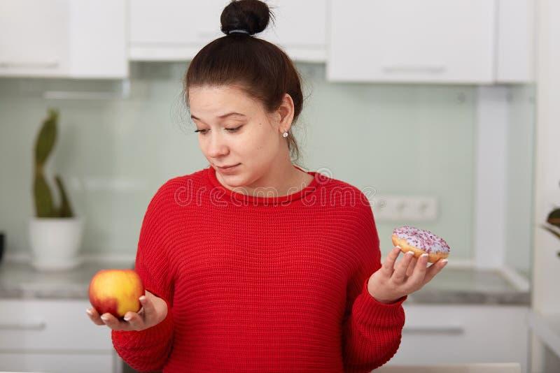 Retrato da mulher pragnant que decide escolher o alimento saudável ou insalubre, levantando no fundo interior da cozinha branca, fotos de stock