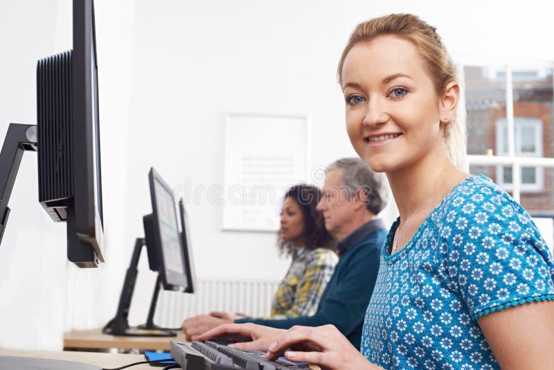Retrato da mulher que atende à classe do computador foto de stock