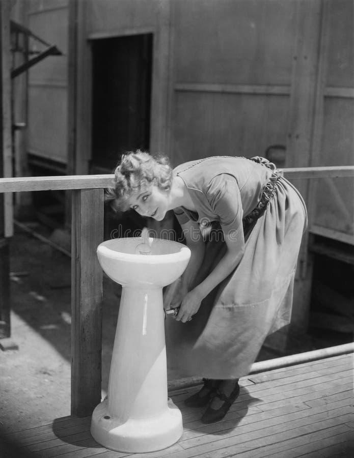 Retrato da mulher que bebe da fonte de água (todas as pessoas descritas não são umas vivas mais longo e nenhuma propriedade exist foto de stock
