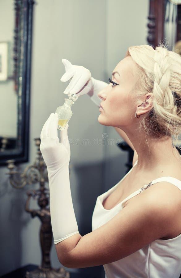Retrato da mulher que cheira um frasco do perfume imagens de stock