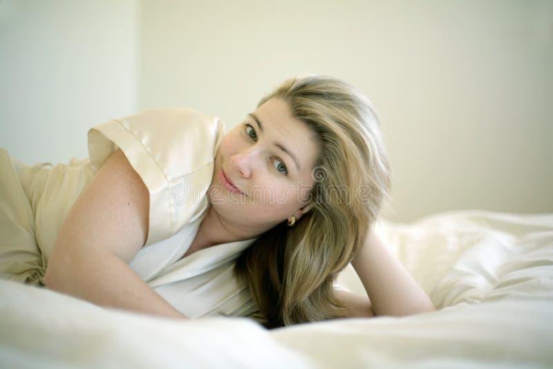 Retrato da mulher que coloca na cama imagem de stock