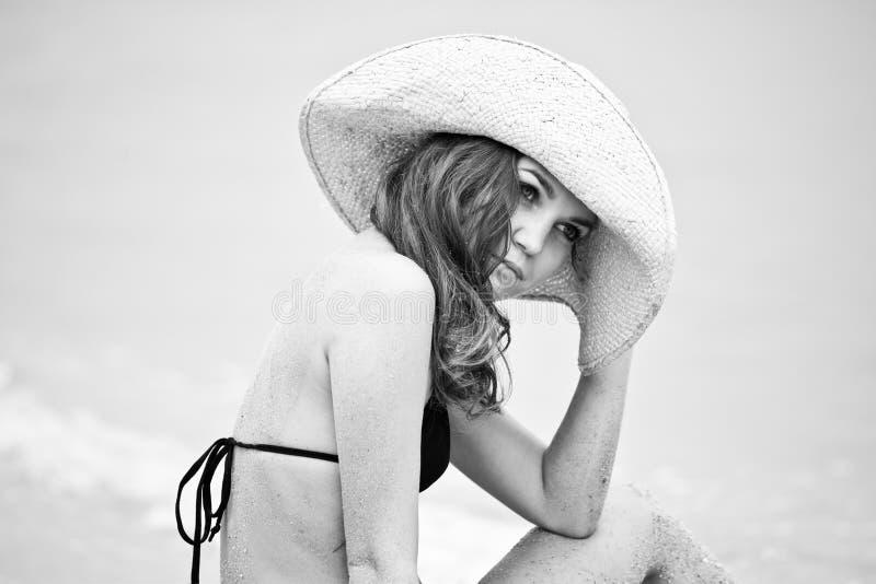 Retrato da mulher que encontra-se na praia da areia imagem de stock